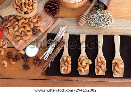Roasted cashews nuts with natural on wood background - stock photo
