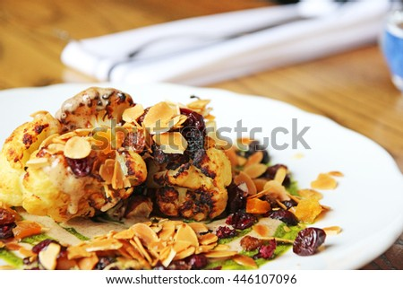 Roasted cauliflower with dried fruit, almond, brown butter emulsion, green herbs - stock photo