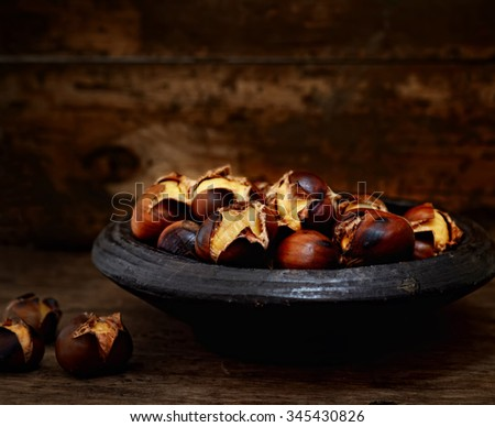roasted chestnuts in a bowl on a wooden background - stock photo