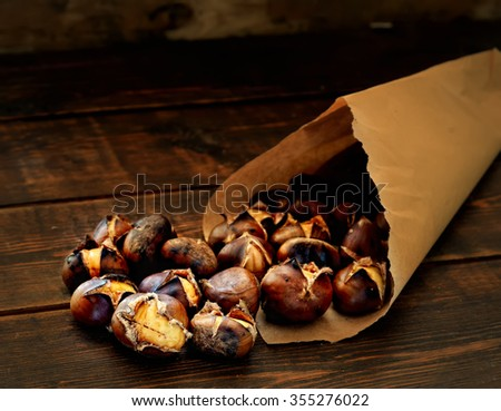 roasted chestnuts in paper bags on a wooden background - stock photo