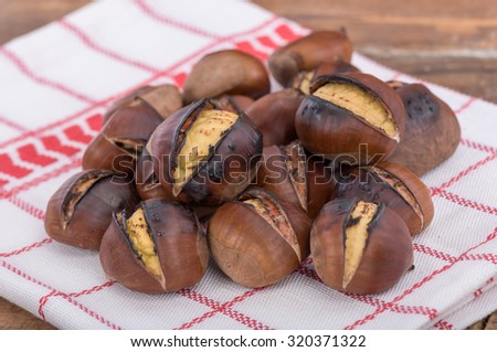 Roasted chestnuts on a towel - stock photo
