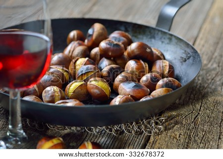 Roasted chestnuts served in a chestnut pan on an old wooden table with a glass of Italian red wine - stock photo