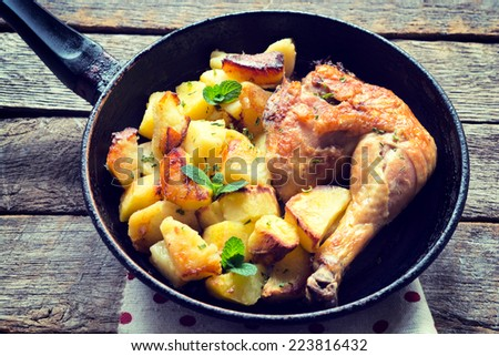 Roasted chicken and baked potato.Selective focus in the middle  - stock photo