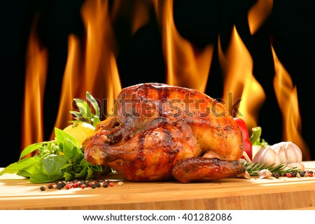 Roasted chicken and various vegetables on a chopping wood  - stock photo