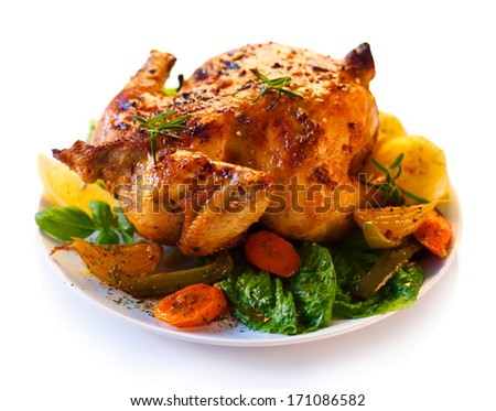 Roasted chicken and vegetables on white background - shallow DOF - stock photo