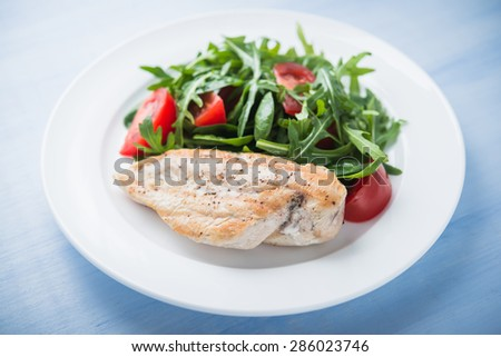 Roasted chicken breast and fresh salad with tomato and greens (spinach, arugula) close up on blue wooden background. Healthy food. - stock photo