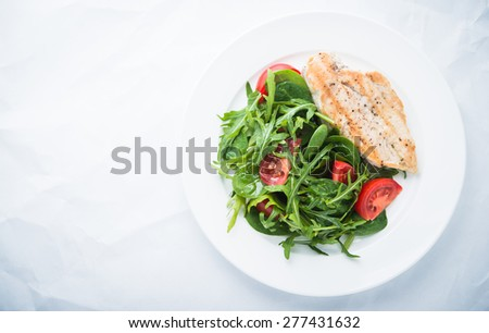 Roasted chicken breast and fresh salad with tomato and greens (spinach, arugula) top view on white textured background. Healthy food. Space for text. - stock photo