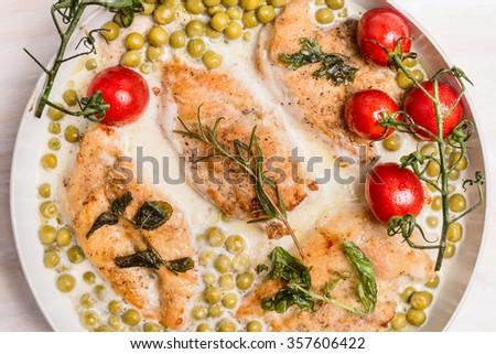 Roasted chicken breast in cream sauce with green pea and tomatoes, top view close up - stock photo