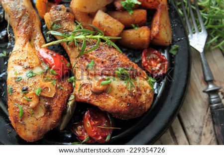 Roasted chicken legs with fresh herbs and fried potatoes - stock photo