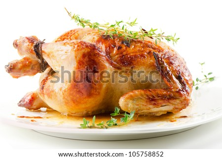Roasted chicken on white plate with thyme - stock photo