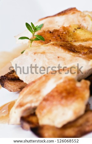 Roasted chicken over sliced potatoes closeup - stock photo