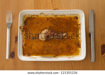 roasted chicken thigh laying on plate in gravy - stock photo