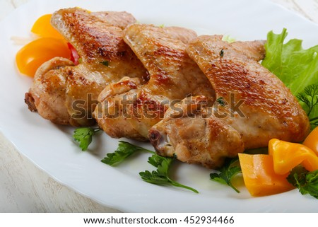 Roasted Chicken wings served salad leaves and parsley - stock photo