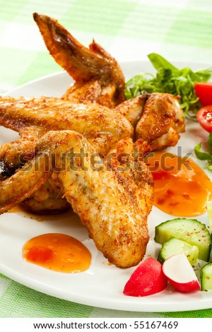 Roasted chicken wings with vegetables - stock photo