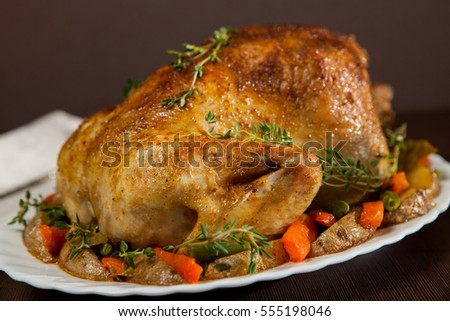 Roasted chicken with a golden crust with vegetables and thyme