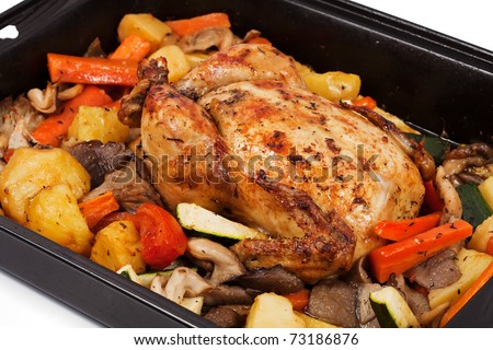 Roasted chicken with assortment of vegetables: potatoes, onions, mushrooms, carrots and zucchini