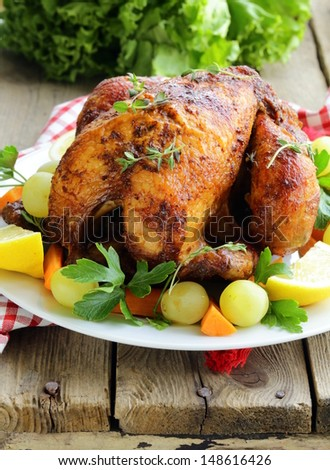 roasted chicken with herbs served on a plate with vegetables and grapes - stock photo