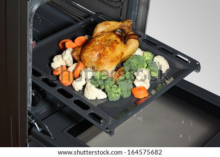 Roasted chicken with vegetables in the oven - stock photo