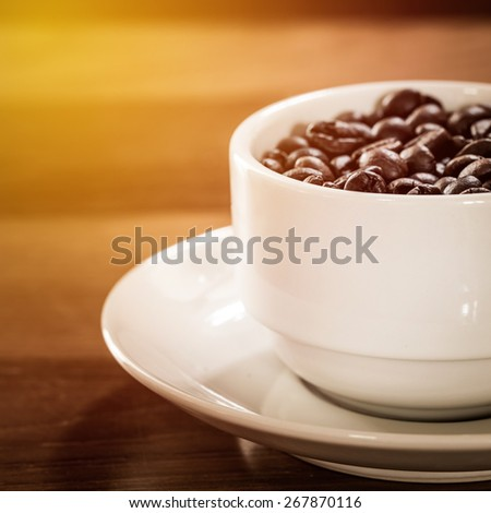 Roasted coffee bean in white coffee cup. Vintage filter. - stock photo