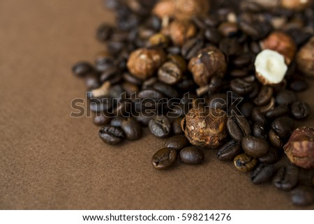 Roasted coffee beans and whole hazelnuts background texture