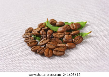 roasted coffee beans decorated with green leaves - stock photo