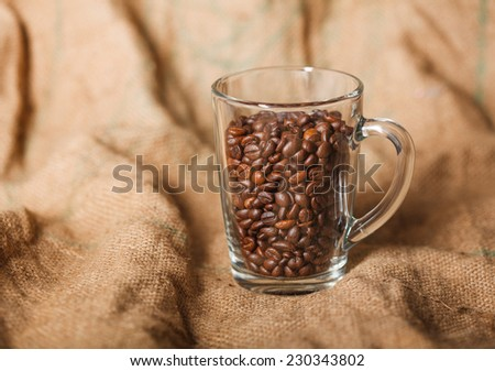 roasted coffee beans in a transparent glass cup on a sack - stock photo
