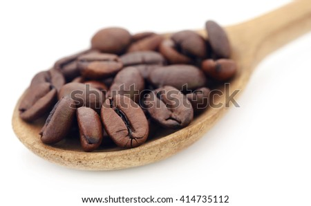 Roasted coffee beans in a wooden spoon over white background - stock photo