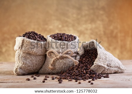 Roasted coffee beans in burlap bags on old table - stock photo