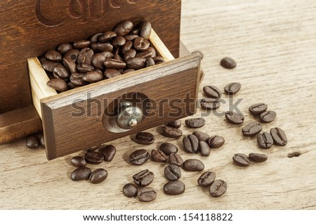 roasted coffee beans in drawer of coffee grinder - stock photo
