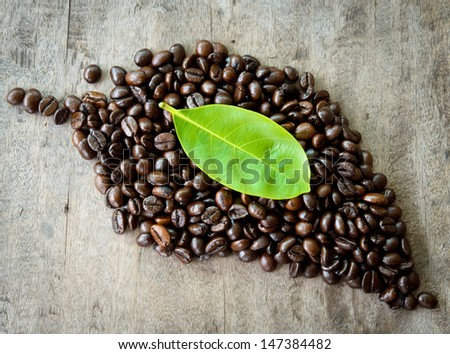 Roasted coffee beans in the shape of a leaf - stock photo