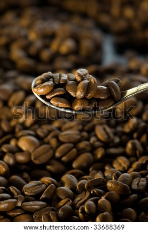 Roasted coffee beans on and around tea spoon. - stock photo