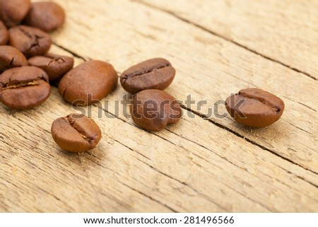 Roasted coffee beans on old wooden table - close up studio shot