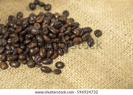 Roasted coffee beans on sack fabric background.