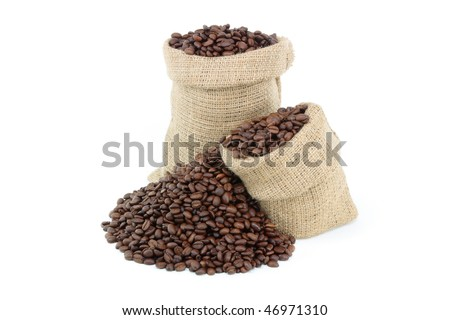 Roasted coffee beans over white.  Still picture displaying roasted coffee beans spilled on pile and in burlap sacks over white background. - stock photo
