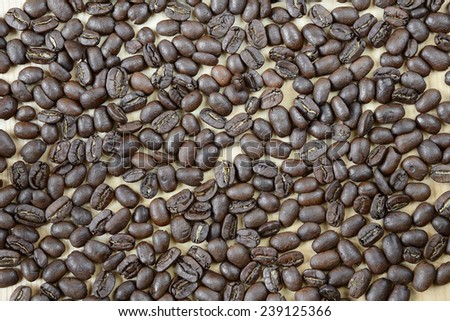Roasted coffee beans scattered on a wooden board - stock photo