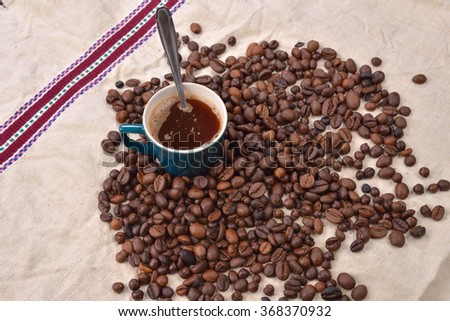 Roasted coffee beans with cup and spoon on jute background. Morning pleasures - stock photo
