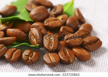 roasted coffee beans with green leaves, scattered on the tablecloth - stock photo