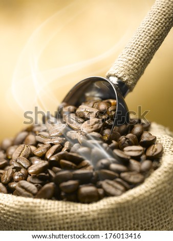 Roasted coffee beans with scoop in yute sack - stock photo