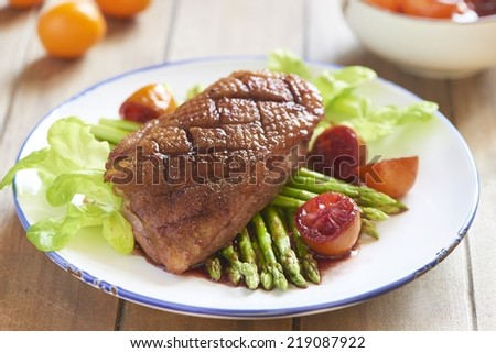 Roasted duck breast with asparagus in citrus sauce - stock photo