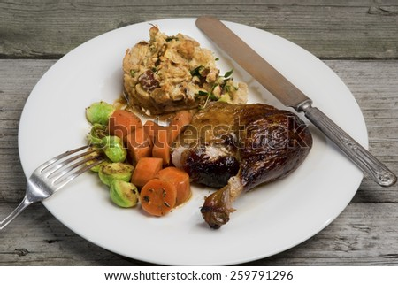 Roasted duck leg with apple and herb stuffing, carrots and Brussels sprouts. Served on a simple white plate on rustic weathered table with vintage silver knife and fork. - stock photo
