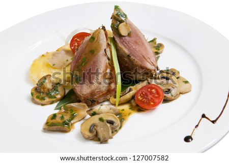 roasted duck meat with mushrooms on a white plate