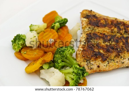 Roasted fillet of salmon served with vegetables. Isolated on the white background.