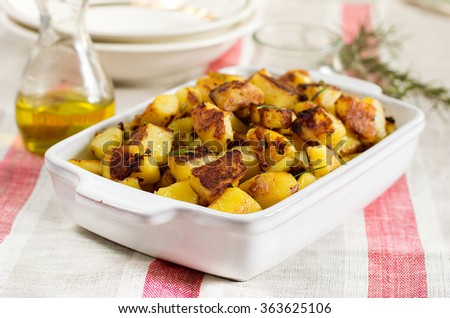 Roasted fried potatoes with garlic and rosemary. Selective focus - stock photo