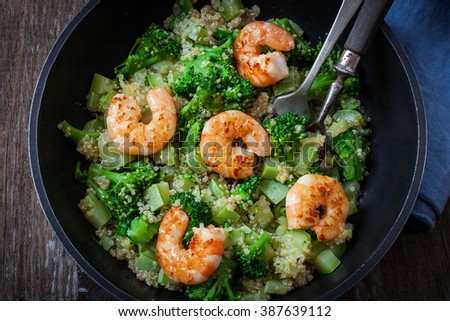 roasted garlic broccoli quinoa salad with prawns on pan