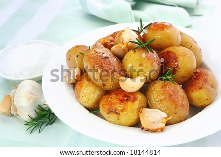 Roasted garlic potatoes with seasalt and rosemary. - stock photo