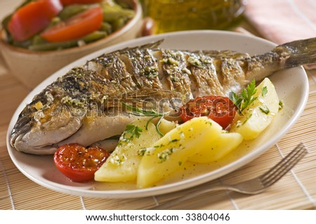 Roasted gilt fish with potatoes and (garlic, parsley) sauce - stock photo
