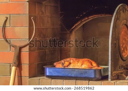 Roasted hot whole duck in baking tray and oven fork at traditional firewood oven background - stock photo