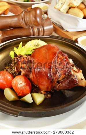 Roasted knuckle of pork with tomatoes and salad - stock photo