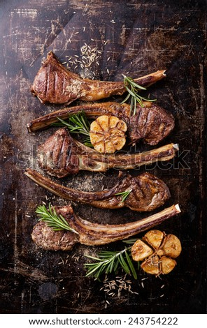 Roasted lamb ribs with spices and garlic on dark steel background - stock photo