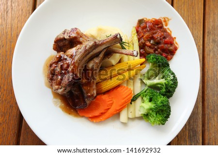 Roasted lamb with tomato sauce and fresh vegetables - stock photo